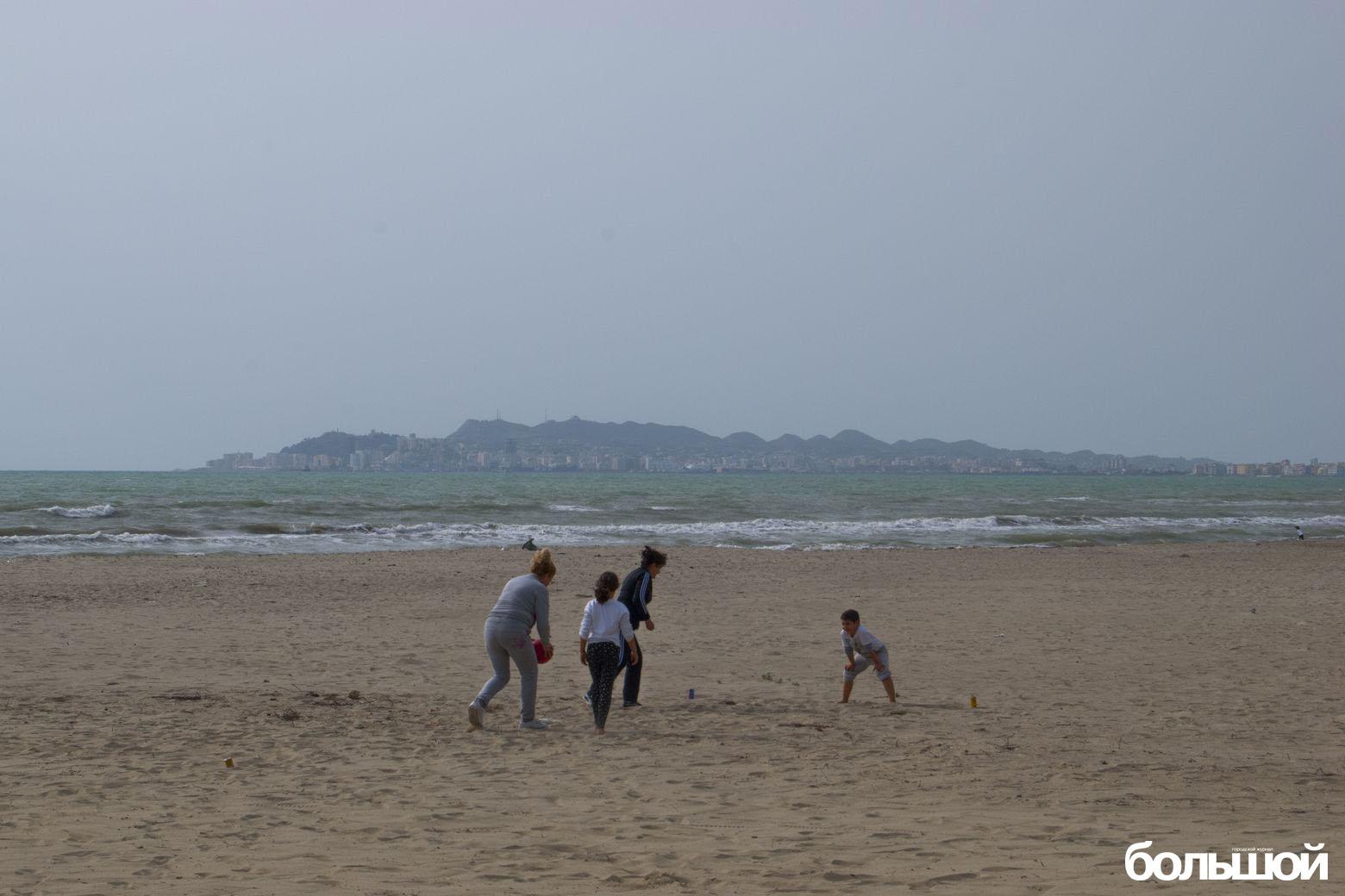 Люди играют в футбол на пляже