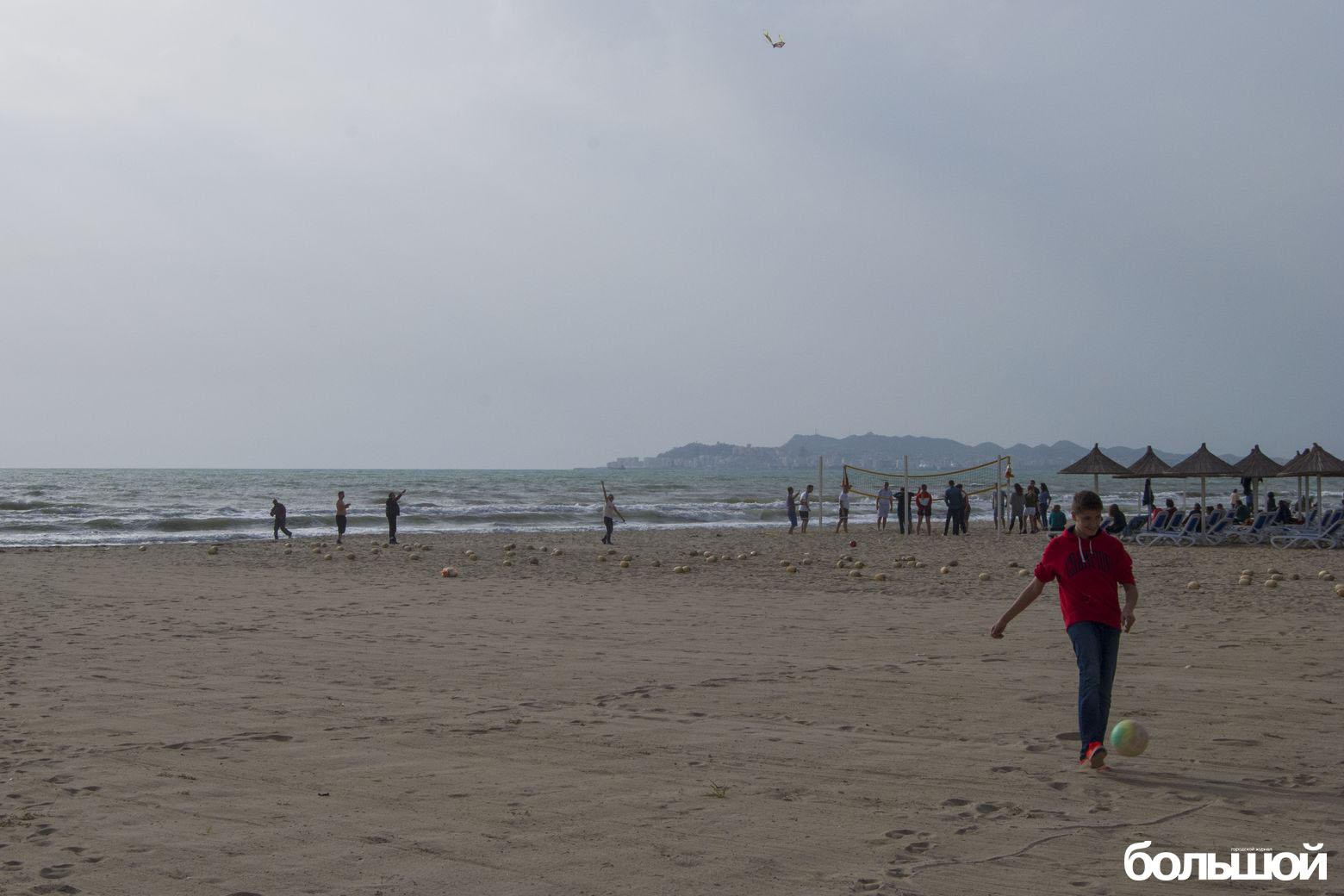 Парень бьет мяч на пляже