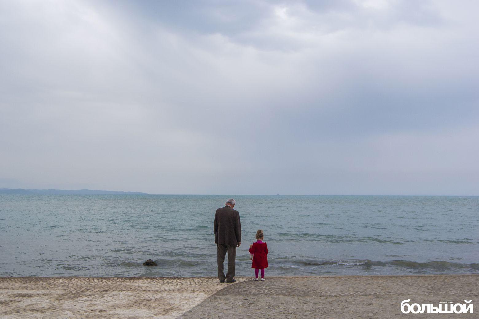 Дедушка с внучкой в красном на фоне моря