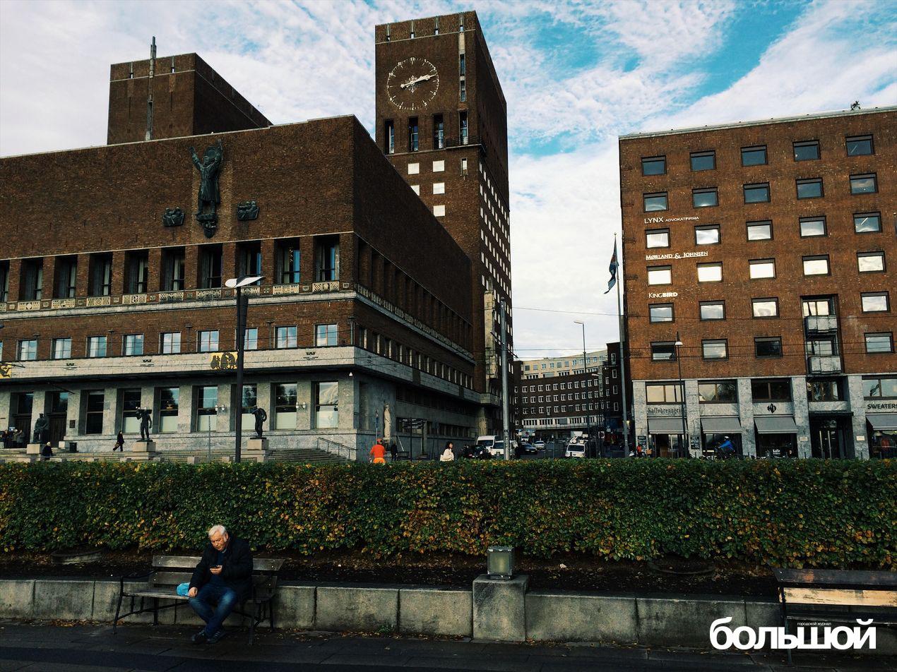 Мужчина сверяет часы своего телефона и городской ратуши